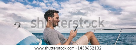 Yacht luxury lifestyle young man using cellphone banner panorama. Person relaxing on deck texting sm Stock photo © Maridav
