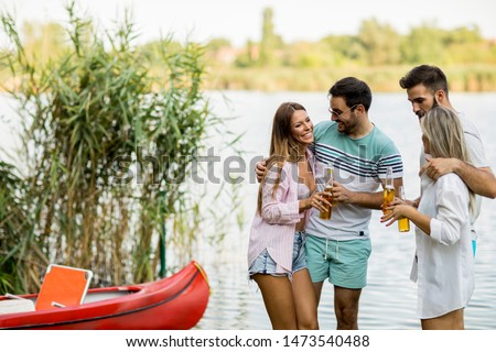 Group of friends with cider bottles standing by the boat near th Stock photo © boggy