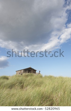 Stock photo: distant view of young couple relaxing in wooden beach hut amongs