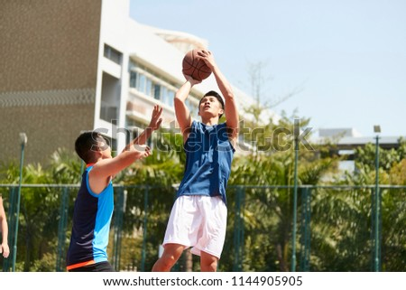 Young basketball player trying to defend the ball from attack of rival Stock photo © pressmaster