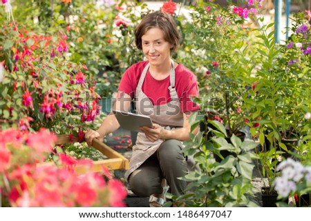 young seller of garden flowers with touchpad checking information stock photo © pressmaster