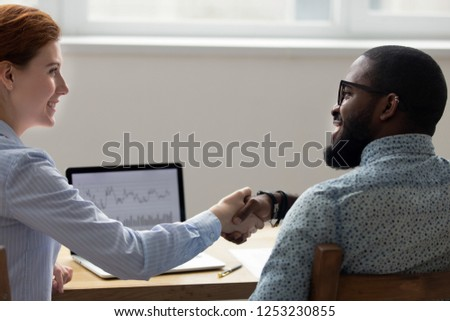 View of two multicultural businesswomen shaking hands and looking at one another Stock photo © pressmaster
