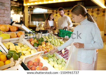 Pretty casual girl taking green apple from display before putting it into packet Stock photo © pressmaster