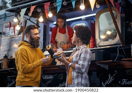 Smiling friends interacting with each other in food truck van Stock photo © wavebreak_media