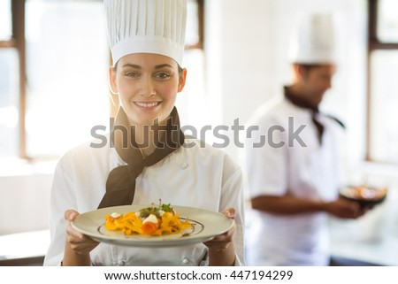 Male and female chefs holding plate of prepared pasta in kitchen at hotel Stock photo © wavebreak_media