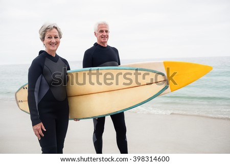 front view of active senior couple standing with surfboard on the beach against mountains background stock photo © wavebreak_media
