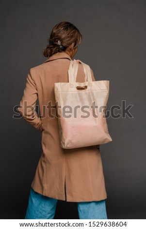 Rear view of young woman in coat and jeans holding textile tote bag on shoulder Stock photo © pressmaster