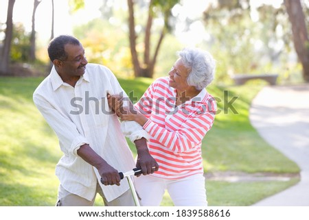 Stock photo: Front view of senior woman pushing happy senior man in a wheelchair on sunny day  in garden