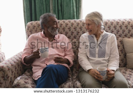 Front view of senior men interacting with each other while having coffee in living room at home Stock photo © wavebreak_media
