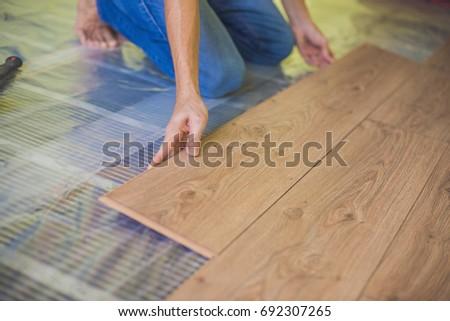 Man installing new wooden laminate flooring. infrared floor heating system under laminate floor Stock photo © galitskaya