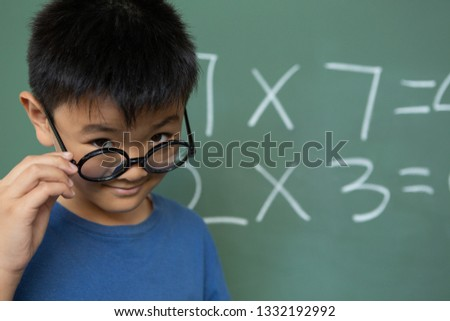 Front view of Asian schoolboy looking over spectacle in a classroom at elementary school Stock photo © wavebreak_media