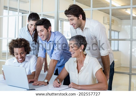 Side view of pretty Caucasian female executive using laptop while coworkers discussing over digital  Stock photo © wavebreak_media