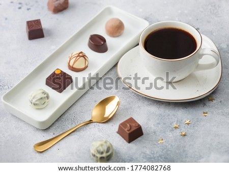 Luxury Chocolate candies in white porcelain plate with cup of black coffee and golden spoon on light Stock photo © DenisMArt