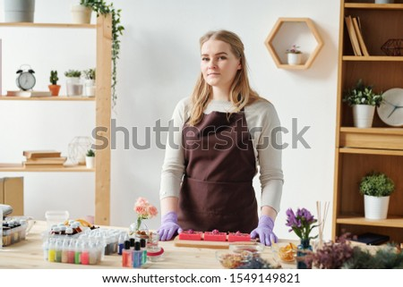 Pretty girl in apron and gloves looking at you during soap making master class Stock photo © pressmaster