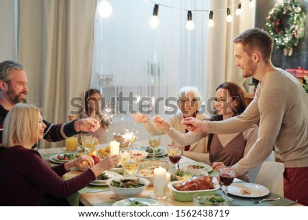 Cheerful young and mature adults holding sparkling bengal lights by xmas dinner Stock photo © pressmaster