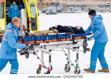 Dois empurrando doente inconsciente homem Foto stock © pressmaster