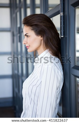 side view of pretty young caucasian businesswoman leaning against wall and using mobile phone in mod stock photo © wavebreak_media