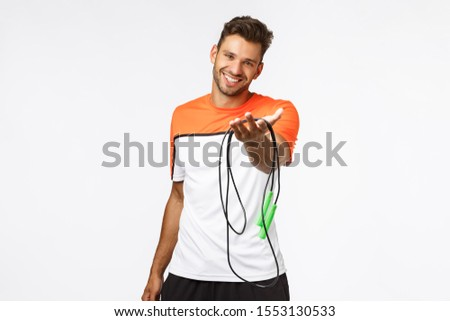 Handsome and cute smiling sportsman extend arm and suggest use his jumping rope, grinning. Charismat Stock photo © benzoix