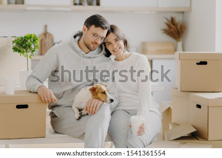 Tired married family couple drink aromatic takeaway coffee, sit closely to each other, pose with ped Stock photo © vkstudio