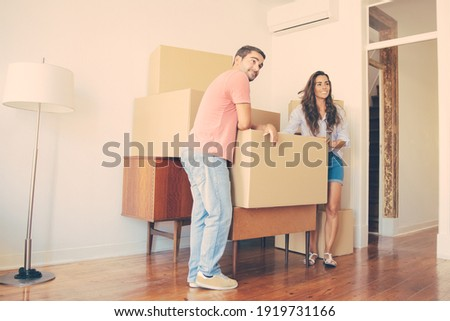 Indoor shot of positive female and male carry carton box with favourite pet, relocate in other place Stock photo © vkstudio