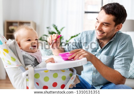 father feeding happy baby in highchair at home Stock photo © dolgachov