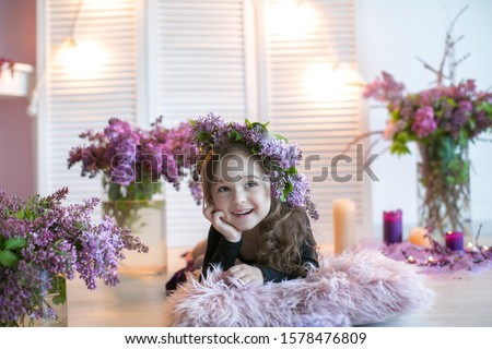 Girl child with a wreath of lilac on his head sits on the floor surrounded by a vase of flowers Stock photo © ElenaBatkova