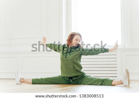 Indoor shot of fit female stretches hand and legs sideways, sits in pose of splits, tilts head on ri Stock photo © vkstudio