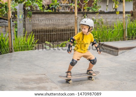 Athletic boy in helmet and knee pads learns to skateboard with in a skate park. Children education,  Stock photo © galitskaya