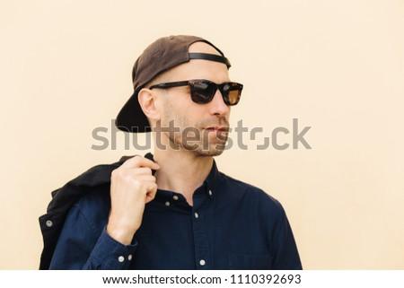 Sideways shot man in fashionable shades, black cap, wears stylish shirt, isolated over beige backgro Stock photo © vkstudio