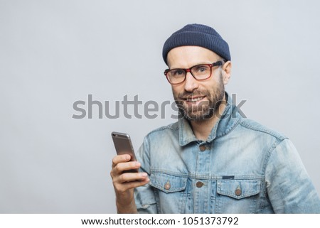 Stusio shot of happy bearded man with stubble holds modern smart Stock photo © vkstudio