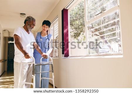 Front view of Asian female nurse helping senior Caucasian male patient to walk with walker in corrid Stock photo © wavebreak_media