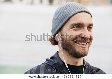 Close up of a motivated young fit sportsman listening to music Stock photo © deandrobot
