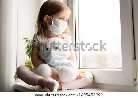 Little girl, child in mask with teddy bear sits on windows, coronavirus quarantine Stock photo © Illia