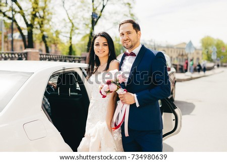 Lovely married couple stand next to each other near car, going in restaurant to celebrate their wedd Stock photo © vkstudio
