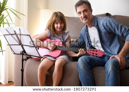 Little girl playing guitar with her music teacher in the rustic  Stock photo © boggy