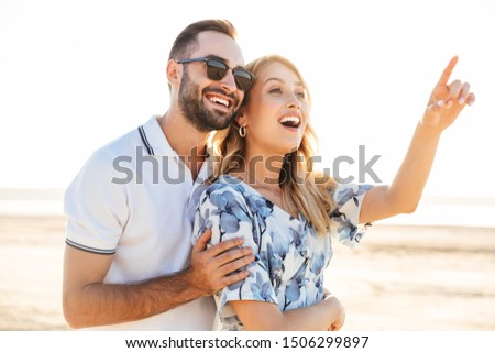Image of two young women pointing fingers upward at copyspace Stock photo © deandrobot