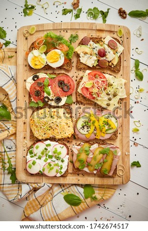 Colorful, different kinds sandwiches served on wooden chopping board. Vegetable toppings Stock photo © dash