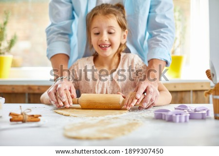 Father showing his little daughter how to roll dough for cookies Stock photo © Illia