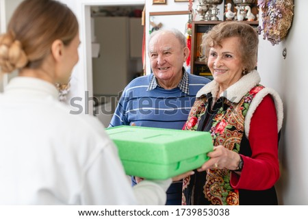 Senior couple greeting volunteer delivering a hot meal to their door Stock photo © Kzenon