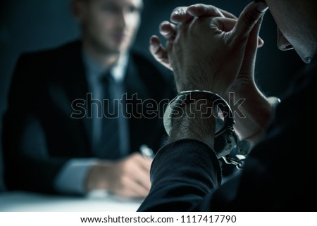 Police officer interrogating suspect or criminal man with handcu Stock photo © snowing