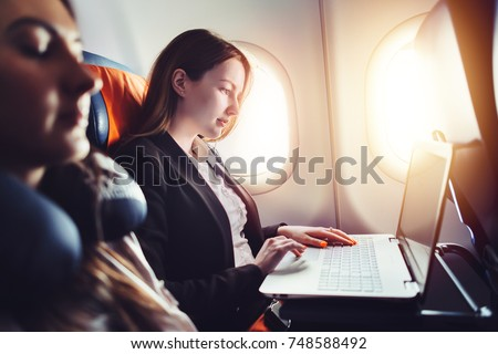 Plane passenger business woman professional working in airplane cabin during flight with in-flight w Stock photo © Maridav