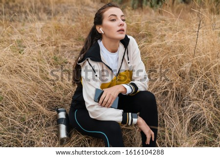 Photo of nice caucasian woman using earpods and smartphone Stock photo © deandrobot