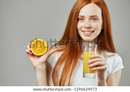 Stock photo: Good looking red-haired female drinking a glass of orange juice while sitting on her bed