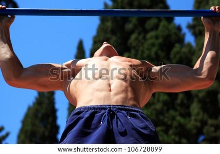 Closeup of young strong teenage athlete doing pull-up on horizon Stock photo © dacasdo