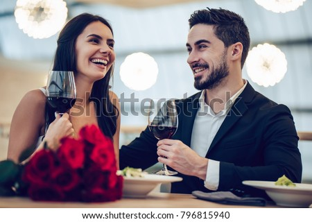 Elegant young woman in a red dress, having a glass of red wine stock photo © lightpoet
