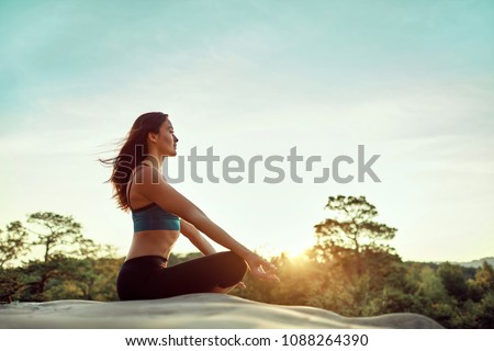 athletic woman relaxing   practicing yoga on the rocks by the se stock photo © vlad_star