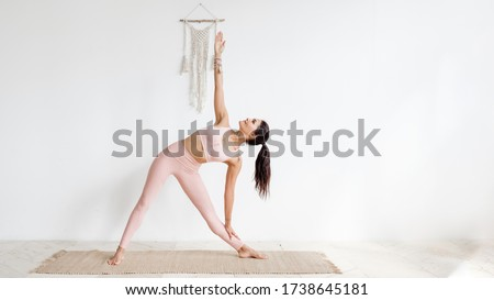 Beautiful sports lady standing and posing in gym while pointing Stock photo © deandrobot