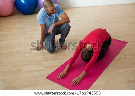 Instructor guiding student in doing child pose at yoga studio Stock photo © wavebreak_media