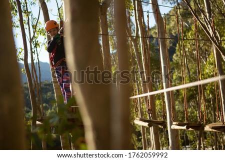 Little girl wearing helmet crossing zip line Stock photo © wavebreak_media