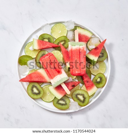 Fruit berry appetizing ice lolly with ice slices on a pink backg Stock photo © artjazz